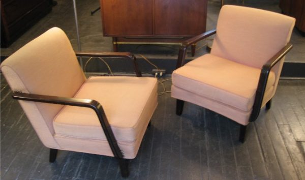 "This Pair of Upholstered Lounge Chairs are attributed to Gilbert Rohde, and look to be early Herman Miller. The seat is low at 15"", and the arms and legs are a dark, rich, Walnut. The seat pads have new foam, and the undersprings and back are nice and tight. The chairs have been redone once quite a while ago, and though they present well as they are, the faded salmon cotton could probably do well with a steam cleaning. Measure 30""d X 25""w X 28""h."