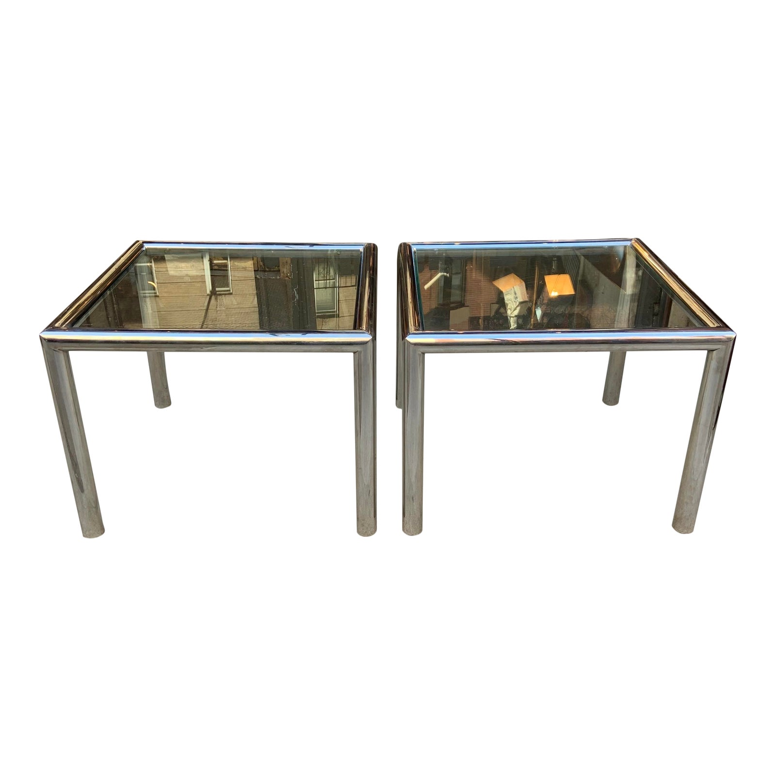 "Pair of ""Tubo"" side tables by John Mascheroni. Constructed of beautifully welded polished aluminum 2 1/2"" cylinders with 3/8"" glass that floats within the frame. Tables retain their adjustable, self leveling glides."