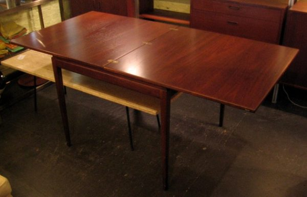 """Jens Risom Walnut Game/Dining Table This Walnut Game/Dining Table was made Jens Risom in the mid 1960s, and is beautifully constructed. The 34"""" square table slides on felt, to reveal a large felt lined storage area in the apron, and flips open to a large 34 X 68"""" dining table. The hinges are inset in the open and closed positions. It is in excellent condition."""